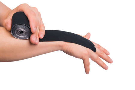 man glues black sports tape on hand from injury isolated on white