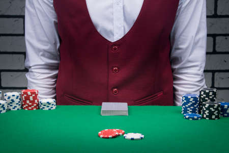 against the background of the croupier a deck of cards and betting chips on the sides on a green table