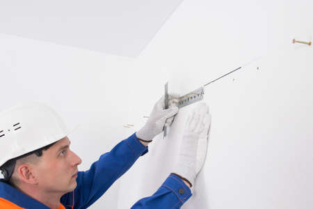 a worker on a white wall, sets a bar for fixing kitchen furniture cabinets