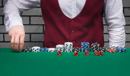 croupier, lays out chips and dice for the Board game blackjack