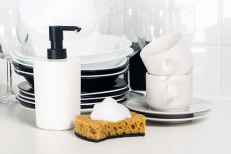 dish detergent and sponge on the counter next to the plates