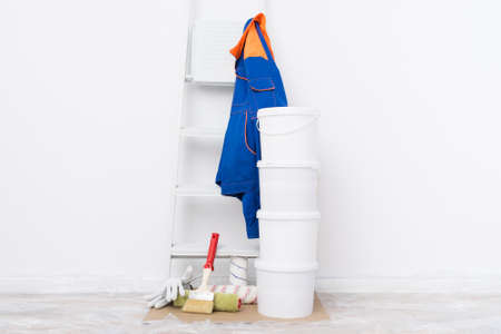 painting equipment for painting walls and buckets of paint on a white background wall
