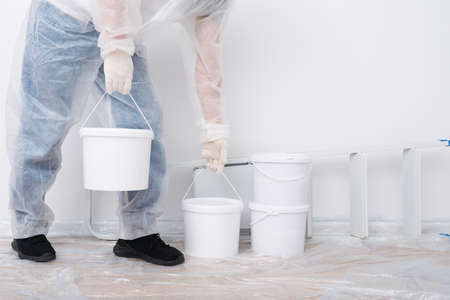a worker in a disposable white overalls brought buckets of paint to renovate the premises