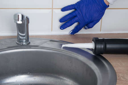 master the finishing of the kitchen, smearing silicone, removing excess and uniform distribution