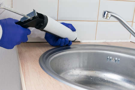 the master of interior decoration, smears the joint of the tile and the kitchen countertop with white silicone instead of the skirting board