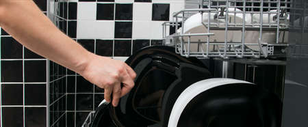a man's hand pulls a clean plate out of the dishwasher