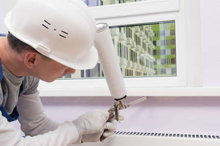 a worker insulates the window sill with mounting foam using a professional gun, close-up Reklamní fotografie