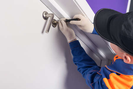 a locksmith in a protective uniform, unscrews a screw with a screwdriver to repair the front door Reklamní fotografie