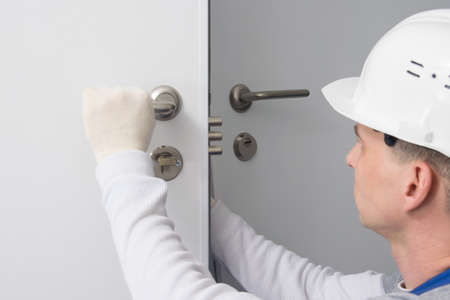 plumber, checks the correct operation of the locking devices of the door lock Reklamní fotografie