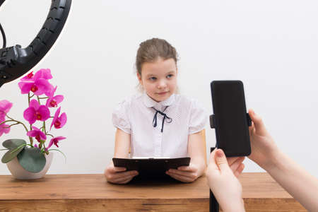 during the break, under the light of the ring lamp, the blogger girl, at the table, is preparing for a video chat, the assistant shows the script and turns on the phone