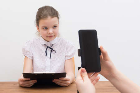during the break, the blogger girl, at the table, is preparing for a video chat, the assistant shows the script and turns on the phone, close-up