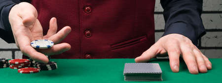 the croupier in hand shows a chip for a small bet for playing cards Reklamní fotografie