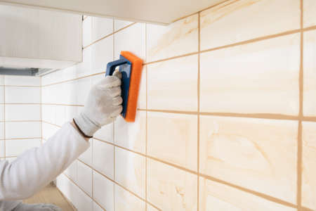 a ceramic tile laying master wipes the seams with a special sponge