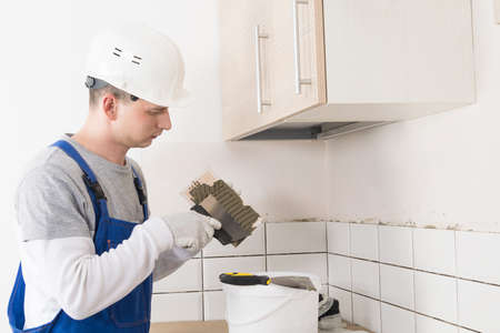 worker applies adhesive to wall tiles, side view