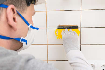 the tiling technician seals the seams with brown putty