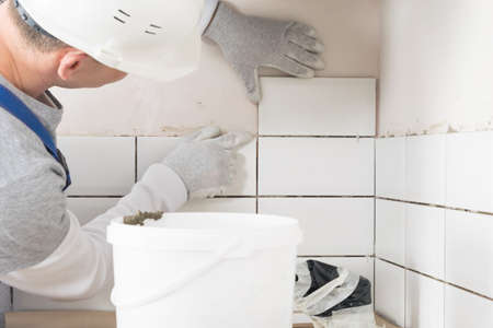 worker glues tiles to the wall, side view