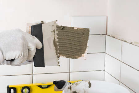 hand with a trowel applies tile adhesive to the wall surface Reklamní fotografie