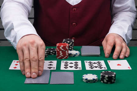 the dealer's hands open cards on the green poker table