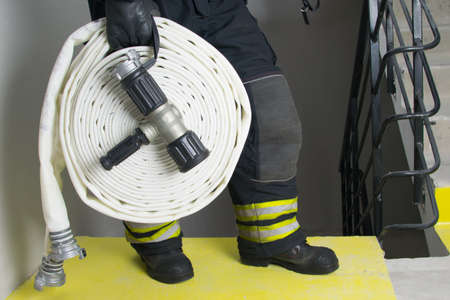 close-up of a white hose and a water supply barrel, in the hands of a firefighter, against the background of the stairs of a residential building