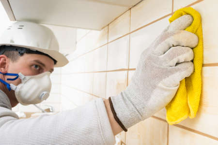 a worker grouting joints after laying ceramic tiles on the wall