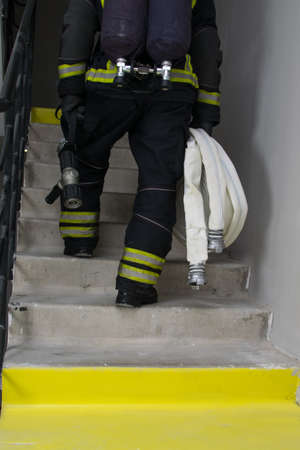 rear view of a firefighter climbing the evacuation ladder of a residential building, there is a place for the inscription below