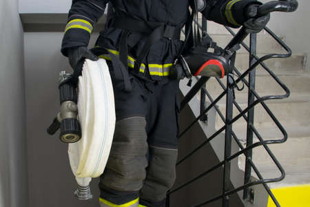 close-up of a firefighter holding water handling equipment, barrel and sleeves