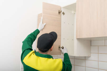 the furniture assembly specialist hangs the fronts on the top cabinet of the kitchen unit
