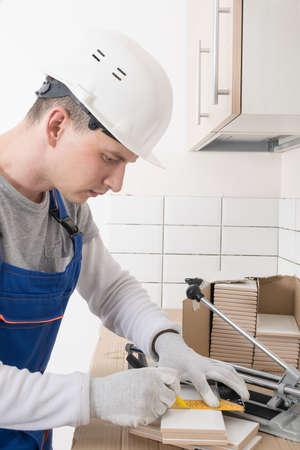the master makes markings on ceramic white tiles for cutting, finishing work