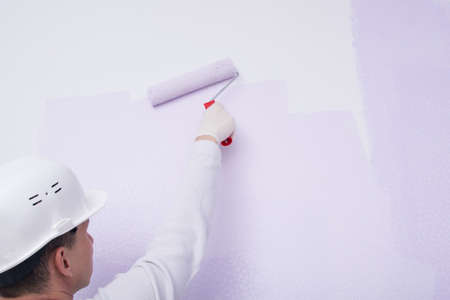 a worker in a white uniform, rear view, paints the wallpaper on the wall with a roller, close-up