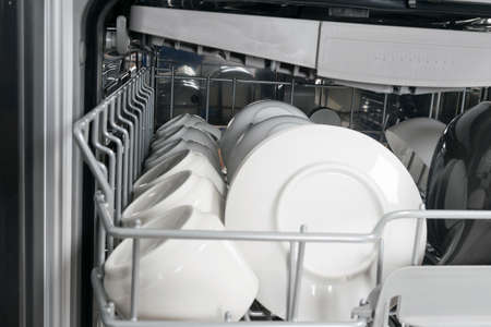 close-up of white saucers and mugs, in the deep compartment of the dishwasher 写真素材