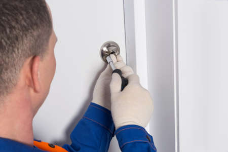 a locksmith in uniform, unscrews the bolt on the front door to close the room from the inside