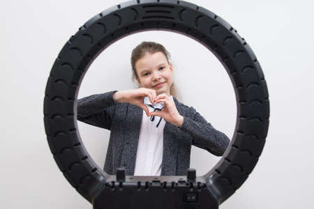 a girl in a gray jacket, in the center of a circular lamp, shows her heart with her hands
