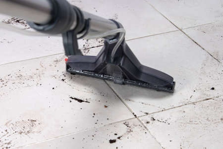 on the white tile floor, a washing vacuum cleaner removes dirty shoe marks after the street, close-up