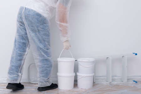 a man in protective clothing, bringing buckets of paint and a set of tools, against a white wall