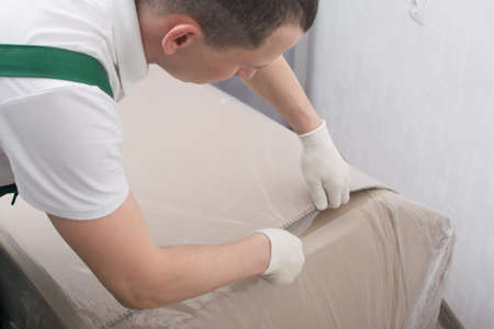 the delivery man in protective gloves, cuts the dense polyethylene, to protect the cardboard from moisture, close-up