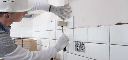 a builder in a protective helmet, using a rubber hammer, corrects the correct installation of tiles