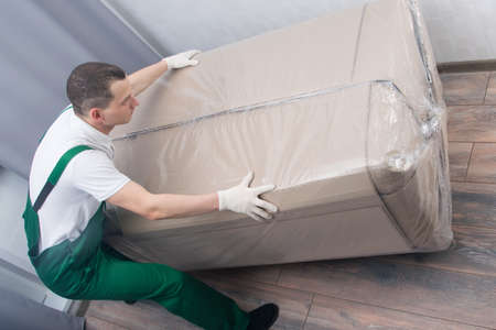 the loader is a man, brought a large box with upholstered furniture, at the address of delivery to the apartment Stock Photo