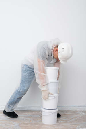 the worker brought buckets of paint and put them against the white wall 写真素材