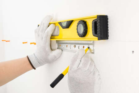 the worker marks the level of the attachment point of the fasteners for hanging the hanging kitchen cabinets