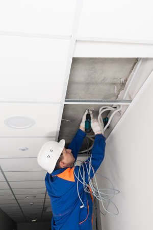 a worker screws the wire holders to the ceiling
