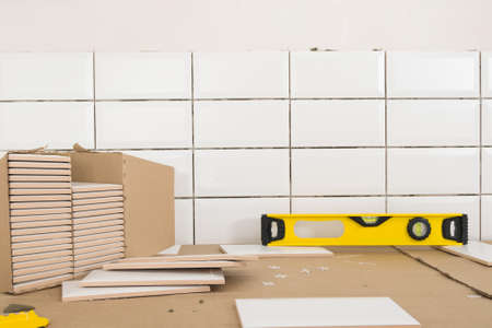 concept of finishing work in the apartment, box with wall tiles and tool - level