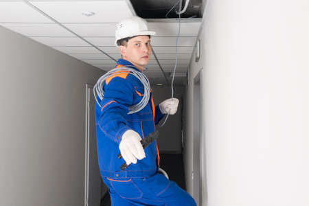 the master of the office Internet installation holds wires and tools in his hands 写真素材