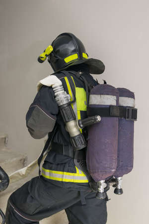 firefighter in special clothes holds a sleeve line, back view