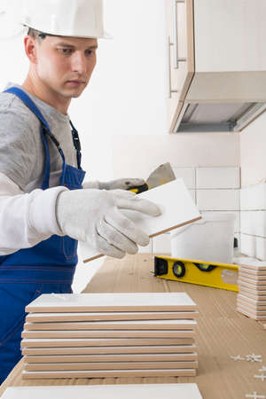 a worker takes a tile from a pile for laying it on the wall, finishing work in an apartment 写真素材