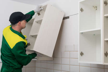 a worker hangs a kitchen cabinet on the wall 写真素材