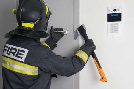 firefighter opens emergency exit door with ax