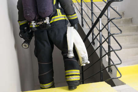 a firefighter carries a hose line and equipment for extinguishing indoor fires