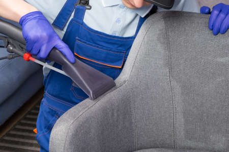 cleaning service worker cleans the drapery of the office chair Standard-Bild