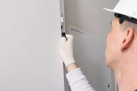 door installation worker adjusts the opening mechanism with a screwdriver