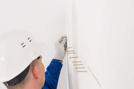 a worker in a helmet inserts self-tapping screws into pre-made holes in a white wall, side view Standard-Bild